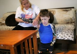Michaela Mitchell helps her 10-year-old son, Jeremiah, take off his prosthetic arms inside their Tulsa home on March 30, 2014.(Photo: Bryan Terry for USA TODAY)